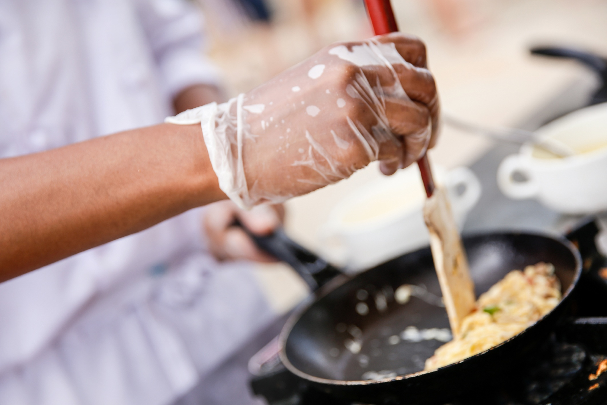 Hand with Disposable Glove Stirring Food
